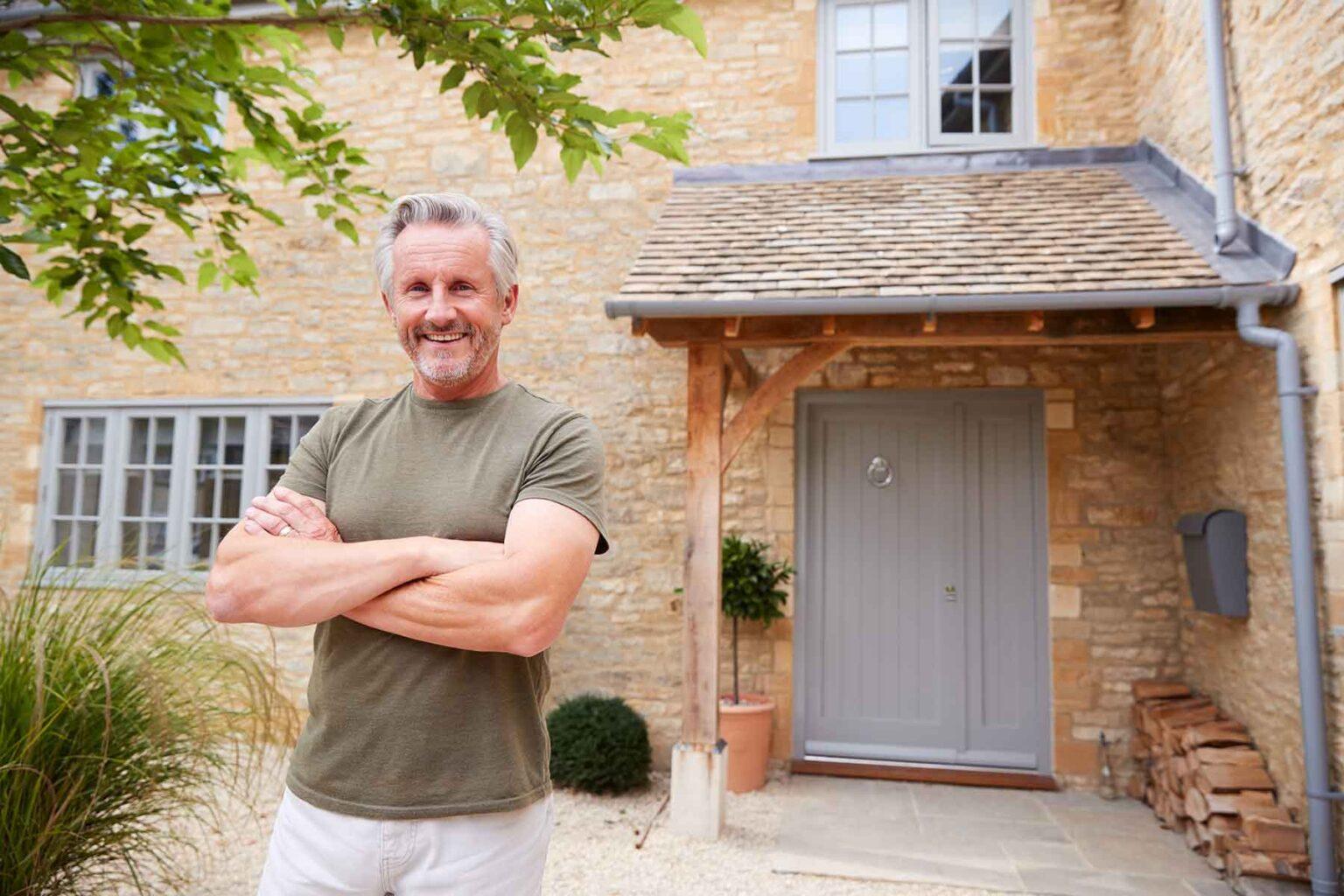 portrait-of-senior-man-standing-outside-front-door-TGQK9MH.jpg